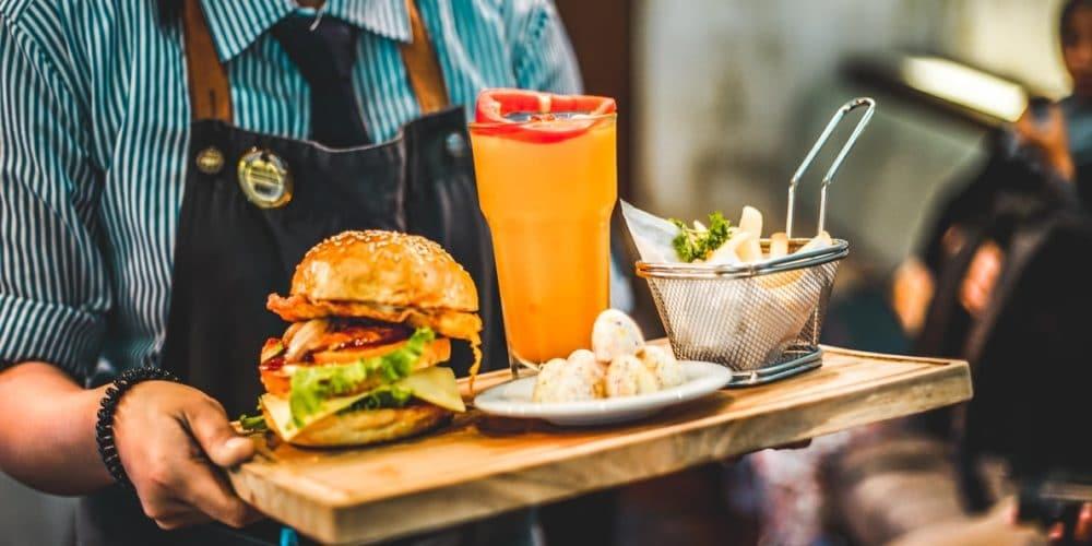 Pincér tálcán hozza egy hamburgert, üdítőt és sült krimplit